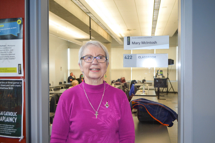 donor smiling while standing beside a classroom dedicated to the memory of mary mcintosh