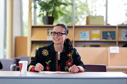 alumnus of distinction award winner Margot Van Sluytman smiling while working in the story arts centre library