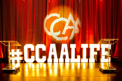 a stage with large letters that say CCAA life and the CCAA logo projected on the curtain on the back wall
