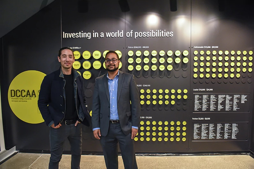 donors smiling while standing by the centennial college downsview campus donor wall