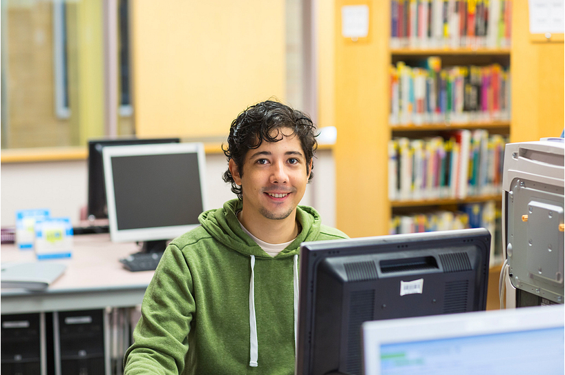 A male student looking for college resources on a computer