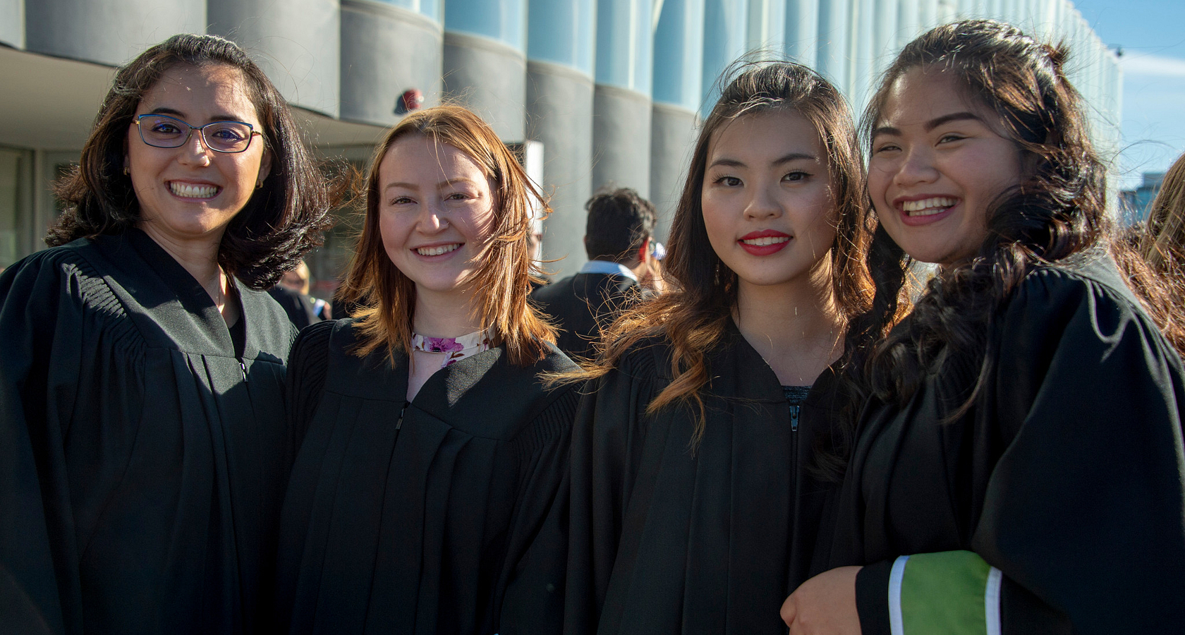 centennial college graduates smiling together at their convocation ceremony standing outside on a sunny day