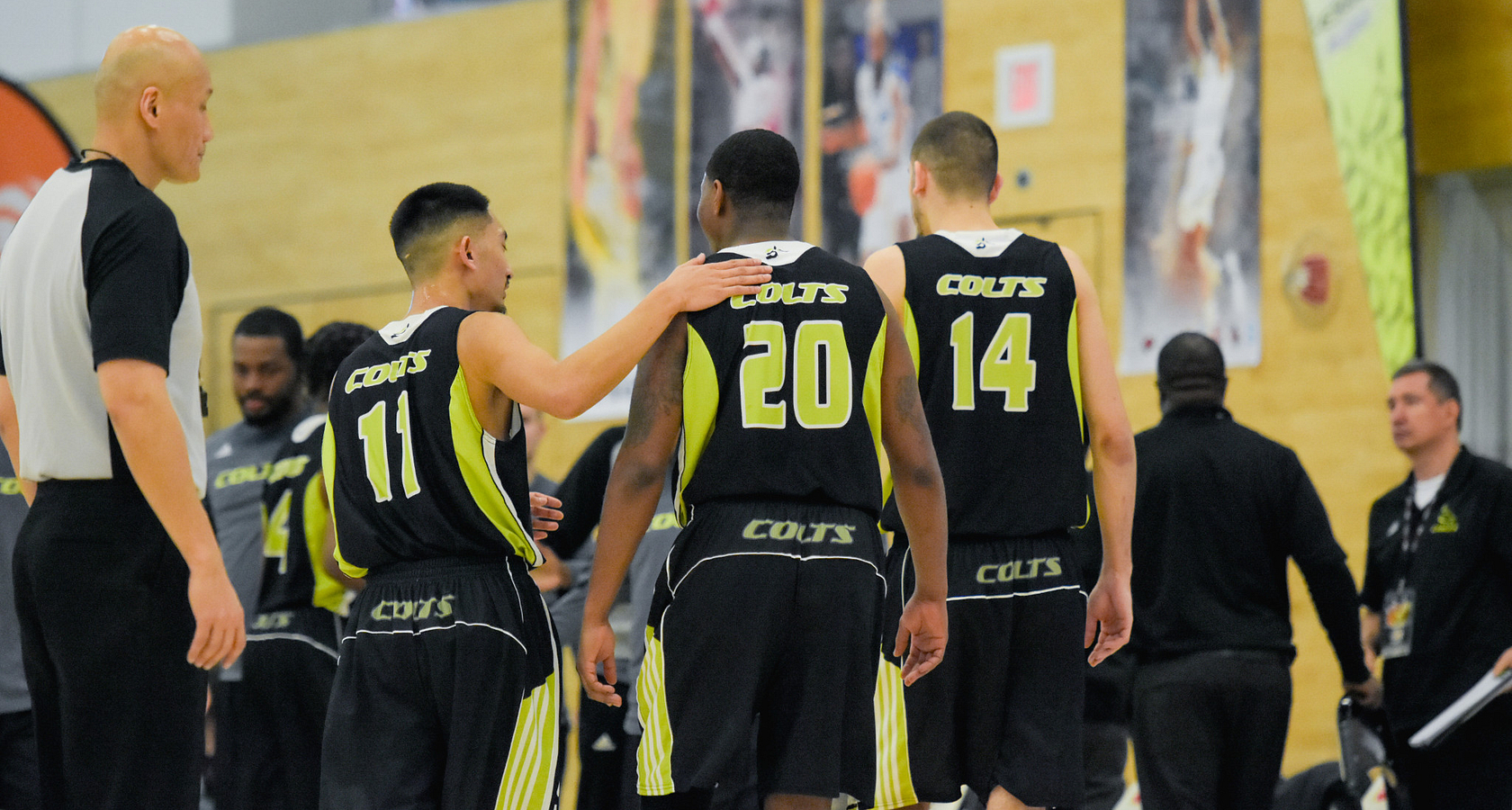 centennial college basketball players patting each other on the back during a game