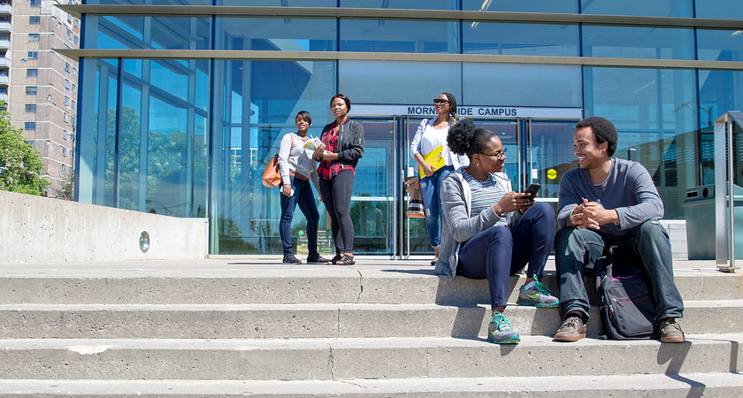 centennial college students smiling while sitting outside on the morningside campus steps talking
