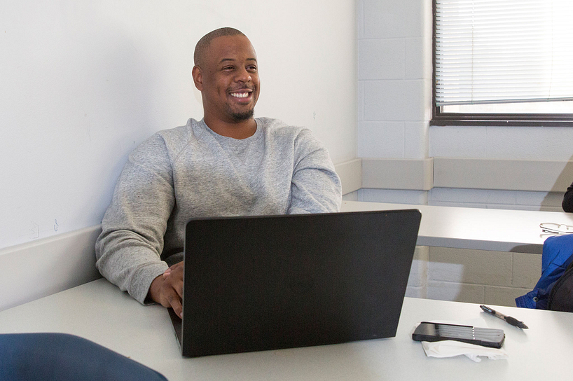 A male student logging into eCentennial on his laptop